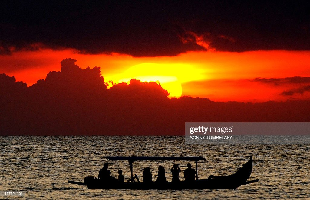 Foreign tourists on a traditional boat enjoy the sunset at Kuta beach in Bali on April 26, 2013. According to data from the Central Statistics Agency (BPS) in February 2013, the number of foreign tourists arriving in Indonesia increased 14.5 percent to 678,400 at the beginning of the year. AFP PHOTO / SONNY TUMBELAKA