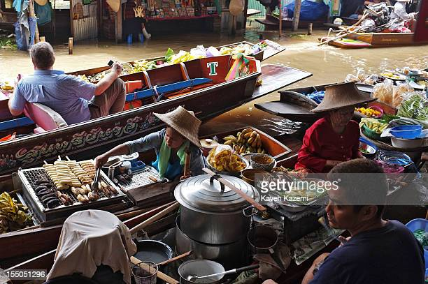 Foreign tourists pass by female Thai vendors preparing food with fresh sea food meat and vegetables on their boats while stationed on the bank of the...