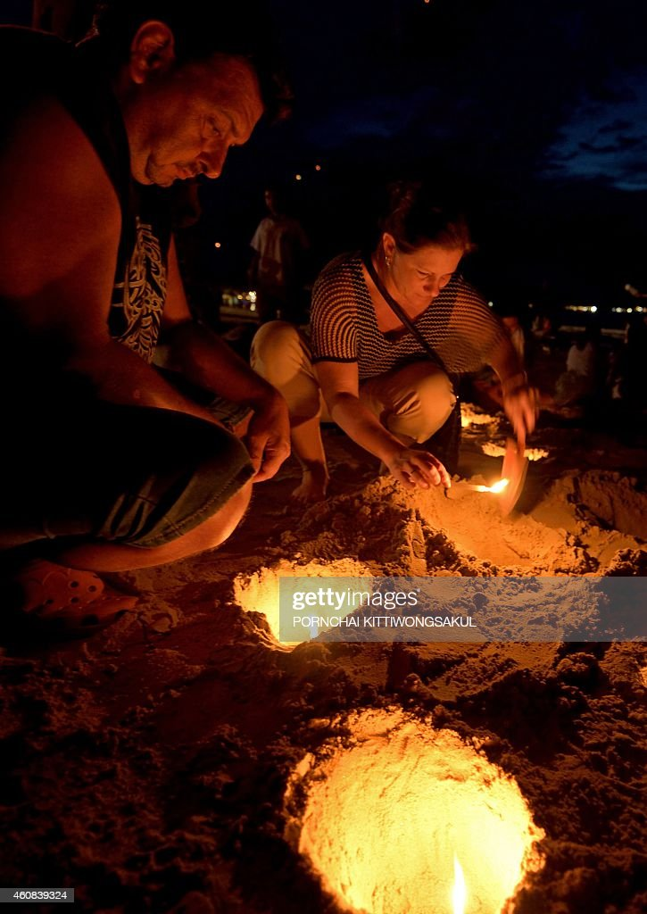 Foreign tourists place candles in the sand during commemorations on the the tenth anniversary of the 2004 tsunami at Patong beach in Phuket province...