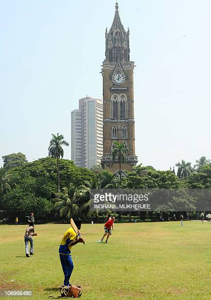 Foreign tourists play cricket with an Indian youth at the Oval maidan landmark in Mumbai near the Bombay University tower on September 27 2010 The...