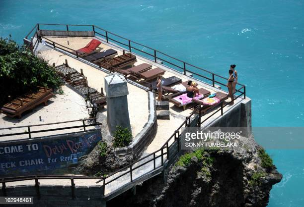 Foreign tourists relax by Uluwatu beach in Jimbaran on Indonesia's resort island of Bali on March 2 2013 According to data from the Central...