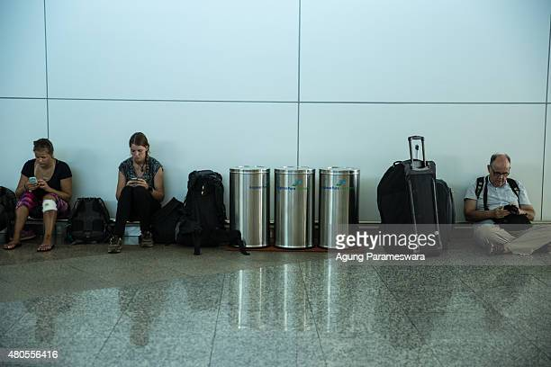 Foreign tourists sit as they wait the flight information at Ngurah Rai international airport departure on July 13 2015 in Denpasar Bali Indonesia...