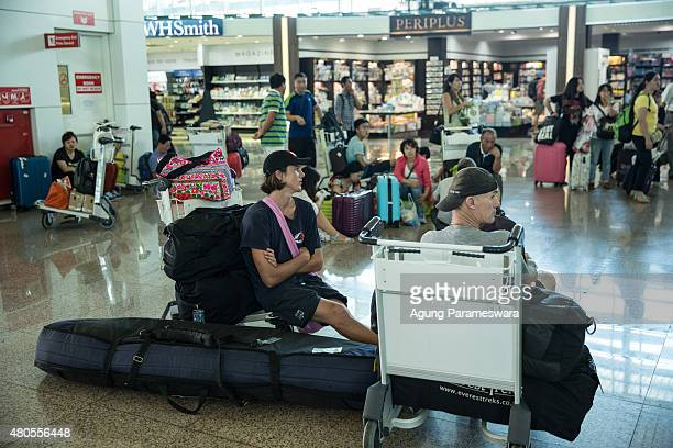 Foreign tourists sit as they wait the flight information at Ngurah Rai international airport departure on July 13 2015 in Denpasar Bali...