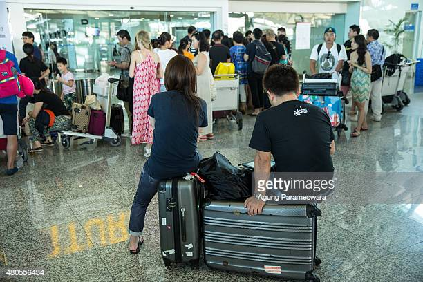 Foreign tourists sit on their luggage as they wait the flight information at Ngurah Rai International airport departure on July 13 2015 in Denpasar...