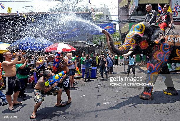 Foreign tourists spray an elephant with water guns as it spouts water during the Songkran festival to mark the Thai new year along the tourist area...
