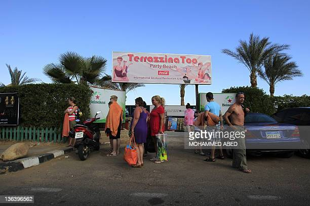 Foreign tourists stand at the entrance of a beach resort in the Red Sea town of Sharm elSheikh some 500 kilometers east of Cairo on January 3 2012...