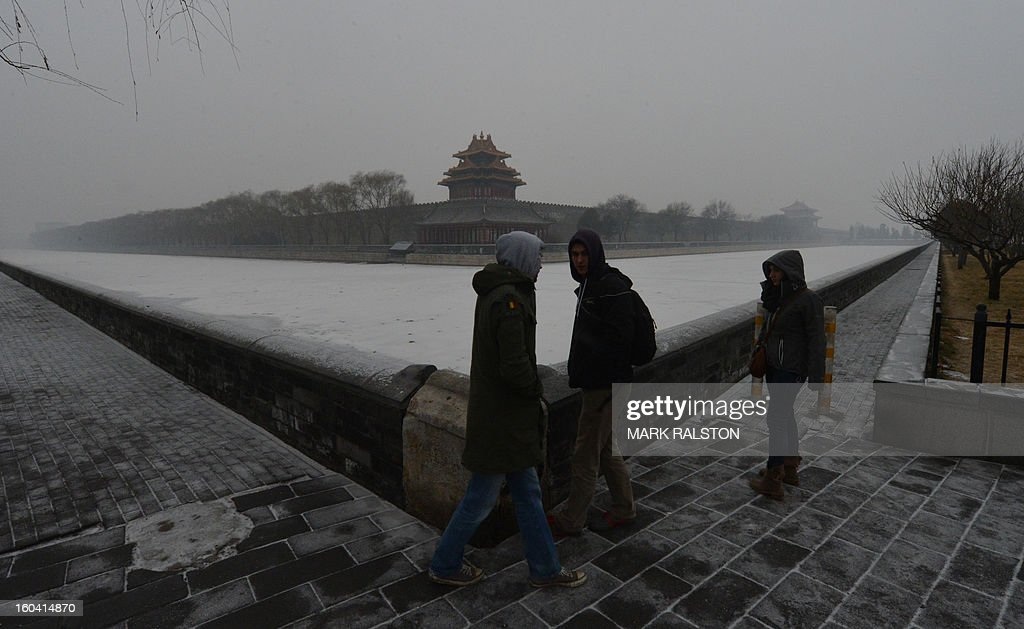 Foreign tourists stand in front of the Forbidden City as smog continues to shroud Beijing on January 31, 2013. Doctors in Beijing said on January 31 that hospital admissions for respiratory complaints rose in recent days during the latest bout of air pollution to cover northern China. AFP PHOTO/Mark RALSTON