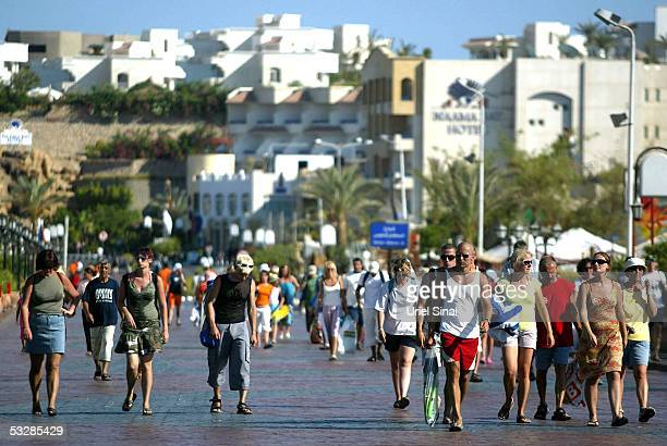 Foreign tourists stroll down Hussein Salem street on July 25 2005 in the Egyptian Red Sea resort of Sharm elSheikh With foreign tourists cutting...