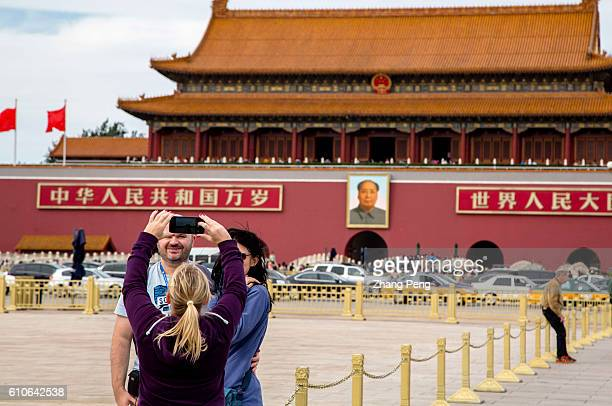 Foreign tourists take souvenir photos in front of Tiananmen Rostrum China will have its 67th National Day on Oct1 2016 To celebrate the National Day...