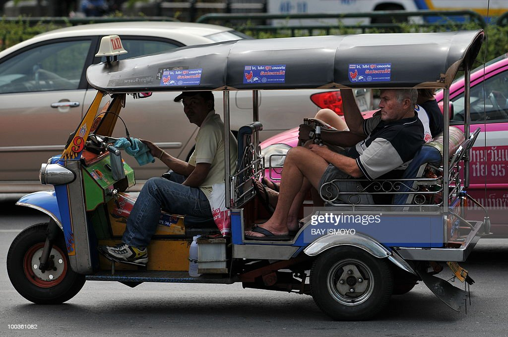 Foreign tourists take tuk-tuk, a three wheeler taxi, to travel at downtown Bangkok on May 24, 2010. Thailand's prime minister said that Bangkok would get back to business on after a massive clean-up, and defended a crackdown on protest rallies that unleashed a rampage of arson and looting. AFP PHOTO / Bay ISMOYO