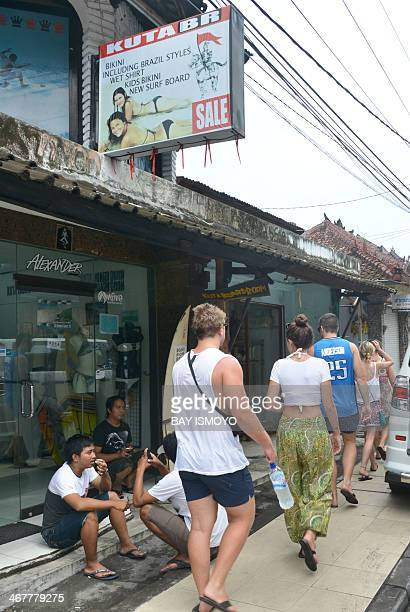 Foreign tourists walk past a surfing and bikini shop belonging to Australian drug trafficker Schapelle Corby's sister Mercedes Corby in Kuta on...
