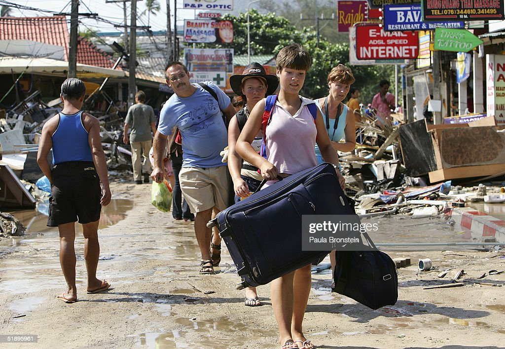 Foreign tourists walk past devastation carrying their luggage as they head to the airport on December 27 2004 along Patong beach one of the worst hit...