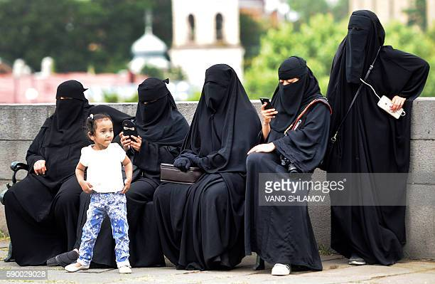 Foreign tourists wearing niqab have a rest on a bench in downtown Tbilisi on August 16 2016 / AFP / Vano Shlamov