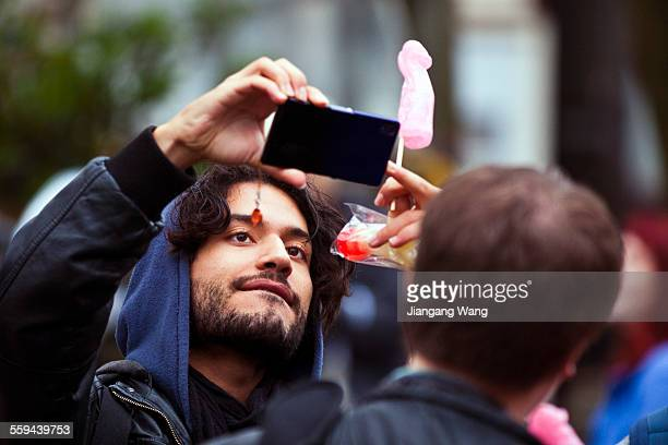Kawasaki Kanagawa Prefecture Japan April 5 2015 Foreign traveler holding penis shaped candies taking pictures with a mobile phone during Kanamara...