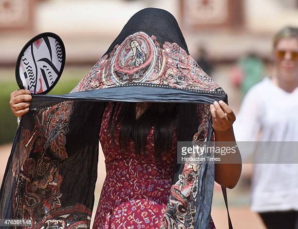 Foreign visitors cover themselves to save from heat during a hot weather at Humayun's Tomb as heat wave conditions prevailed in Northern India as the...