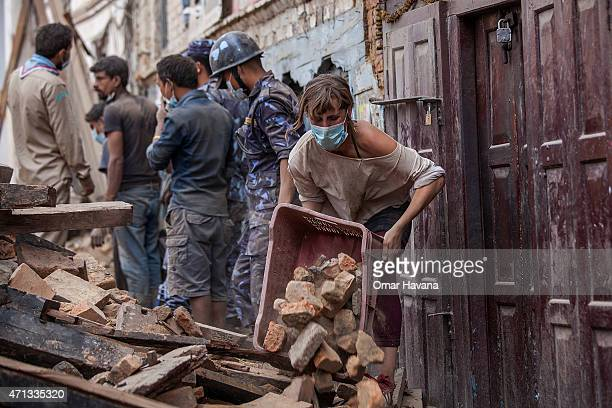 A foreign volunteer clears debris of a collapsed temple at Basantapur Durbar Square on April 27 2015 in Kathmandu Nepal A major 78 earthquake hit...