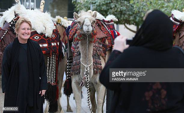 Foreign women take pictures with camels in the background at the Saudi Travel and Tourism Investment Market fair in the capital Riyadh on March 24...
