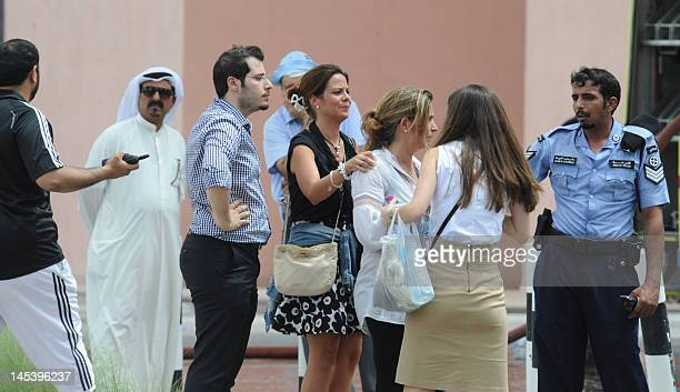 Foreign women talk to a policeman outside Doha's Villagio Mall after a fire broke out at the Gulf emirate's main shopping centre on May 28 killing at...
