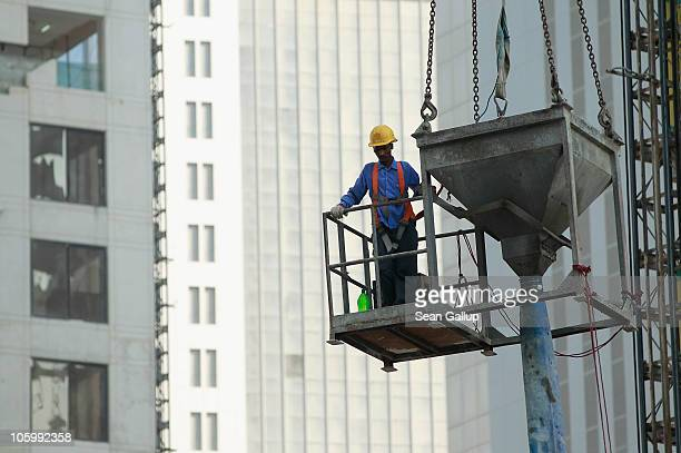 A foreign worker helps guide a concrete funnel hoisted by a crane at a construction site among new highrise office buildings and hotels under...