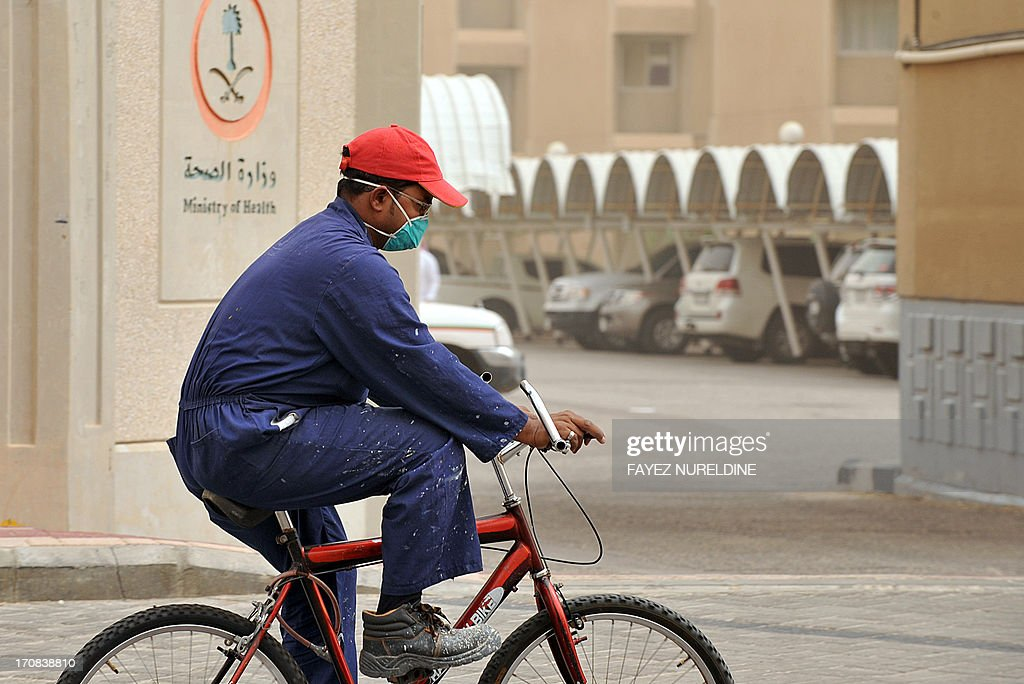 A foreign worker wears a mask as he rides a bicycle near the King Fahad hospital in the city of Hofuf, some 370 kilometres East of the capital Riyadh, on June 16, 2013. In the East of Saudi Arabia, where outbreaks of the MERS virus have been most concentrated, inhabitants have resumed their habits of shaking hands and kissing without worrying too much despite the death toll from the SARS-like virus reaching 32 in the kingdom. AFP PHOTO/FAYEZ NURELDINE
