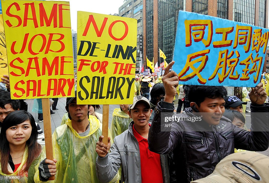 Foreign workers display placards during a May Day rally in Taipei on May 1, 2013. More than 10,000 people took to the streets in Taipei to protest the government's planned pension cuts, including raising labour insurance fees and lowering the payment scale. AFP PHOTO / Mandy CHENG
