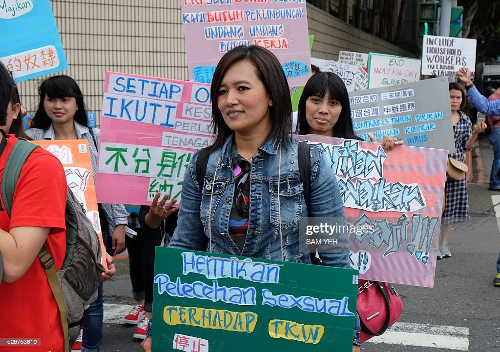 Foreign workers from Indonesia and the Philippines display signs that read 'raise the basic labor's salary' during a demonstration to mark the annual Labor's Day in Taipei on May 1, 2016. Thousands local labors and foreign workers march on the streets in Taipei to demand to protect their basic labor's rights. / AFP / SAM YEH