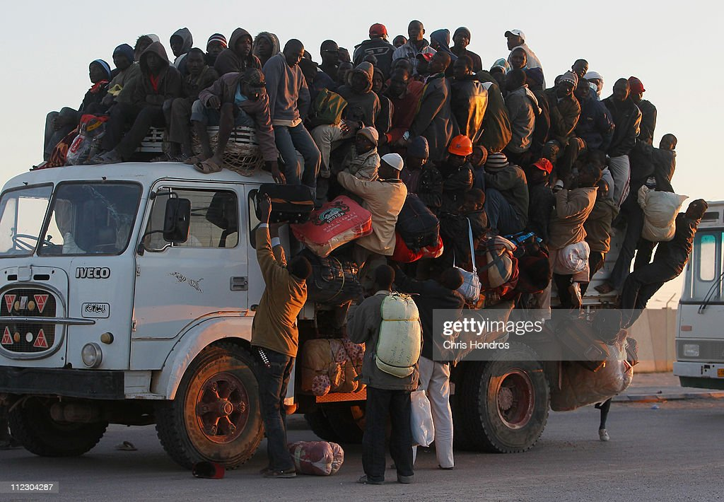Foreign workers from Nigeria, Ghana, and other African countries pile in the back of a truck with their belongings trying to leave the besieged city of Misrata April 18, 2011 as the sun sets on the port in Misrata, Libya. Thousands of foreign workers and Libyans alike are trying to leave war-torn Misrata, as fighting continued between Libyan government forces and anti-government rebels. The Libyan government has come under international criticism for using heavy weapons and artillery in its assault on Misrata, which can cause civilian casualties.