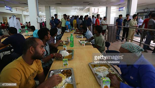 Foreign workers have lunch at the cafeteria of the new labour city in Doha on May 3 which was built by the Qatari government and is currently housing...