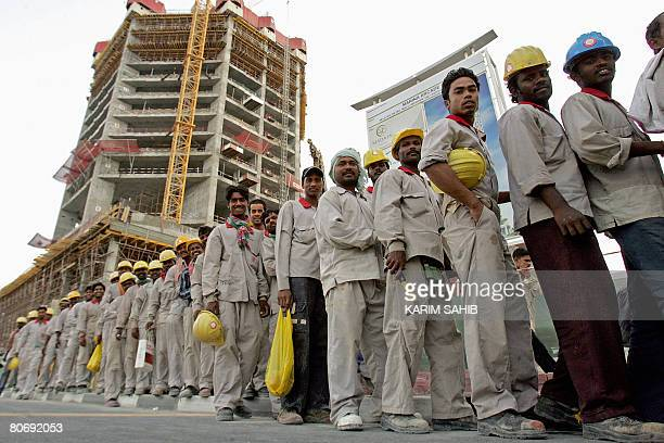Foreign workers stand in line to take a bus that will transport them to where they live at the end of their shift at a construction site in Dubai on...