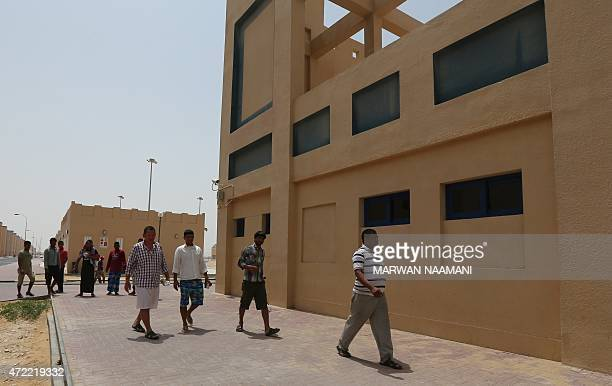 Foreign workers walk outside a building at the new labour city in Doha on May 3 which was built by the Qatari government and is currently housing...