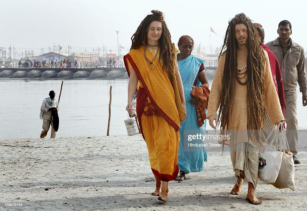 Foreigner devotees dressed like Indian holy men at Sangam (confluence of river Ganga, Yamuna and mythical Saraswati) during Kumbh Mela, on January 16, 2013 in Allahabad, India. Kumbh is World's biggest religious gathering, in which more than 100 million of Hindus and sikh devotees will take part over next 55 days. Apart from being pilgrimage of faith, salvation and hope for millions of devotees, it also serve as meeting ground for the vast spectrum of Indian religious and spiritual views.