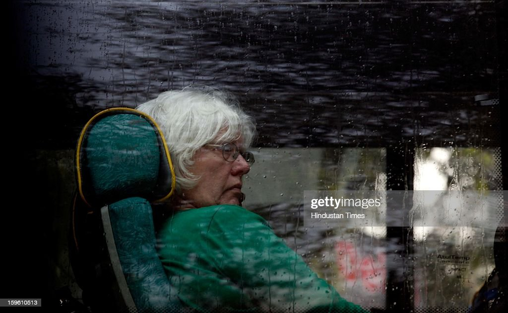 A foreigner lady looking through a glass window during rainfall on January 17, 2013 in New Delhi, India. Capital witnessed light rain and chilly winds even though temperatures were above average.