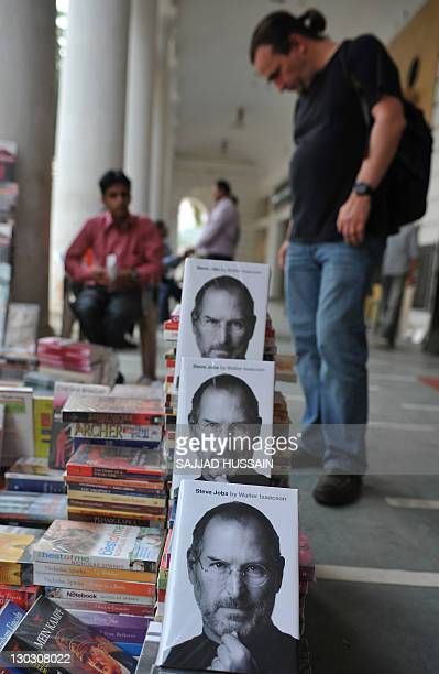 A foreigner looks at books near the new biography of Apple cofounder Steve Jobs at a street market stall in New Delhi on October 26 2011 The eagerly...
