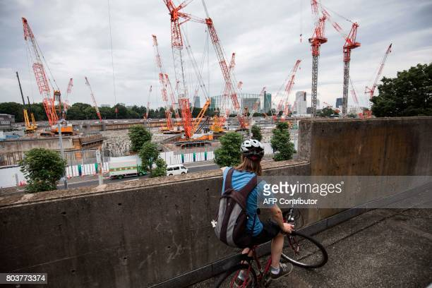 A foreigner looks at the construction site for the National Stadium venue for the upcoming Tokyo 2020 Olympics in Tokyo on June 30 2017 The...