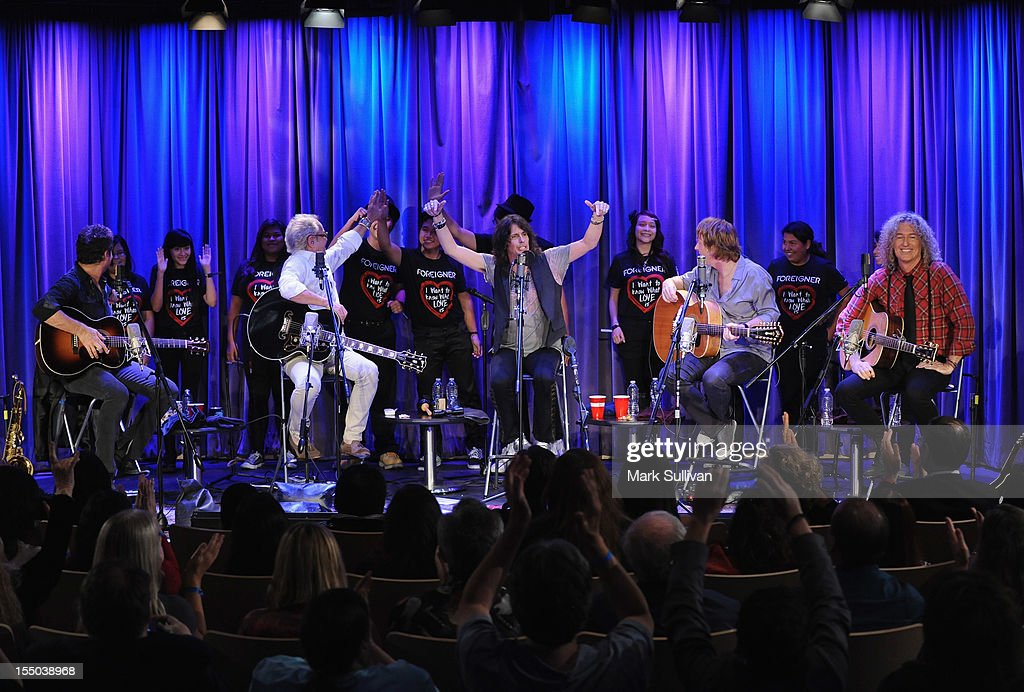 Foreigner members (L-R) Tom Gimbel, Mick Jones, Kelly Hansen, Jeff Pilson and Bruce Watson perform with students from Belmont High School (Los Angeles) during Juke Box Heroes: An Evening With Foreigner at The GRAMMY Museum on October 30, 2012 in Los Angeles, California.