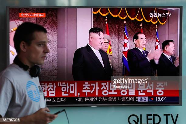 A foreigner walks past a television screen showing an image of Kim Jong Un leader of North Korea center during a news broadcast on North Korea's...