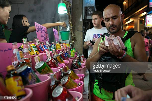 Foreigners attend the Full Moon party buy cheap liquor in buckets from Thai vendors near the beach of Haad Rin on August 21 2013 on Koh Phangan...