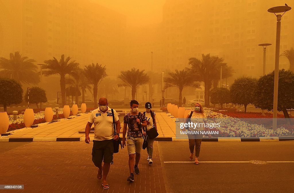 Foreigners wear medical masks as they walk in a street in Dubai amid a sandstorm that engulfed the city on April 02 2015 AFP PHOTO / MARWAN NAAMANI