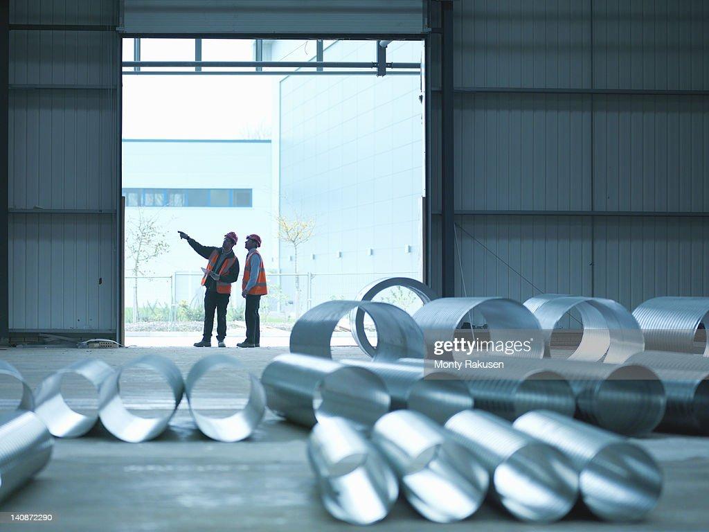 Foreman and apprentice in doorway in factory of building site