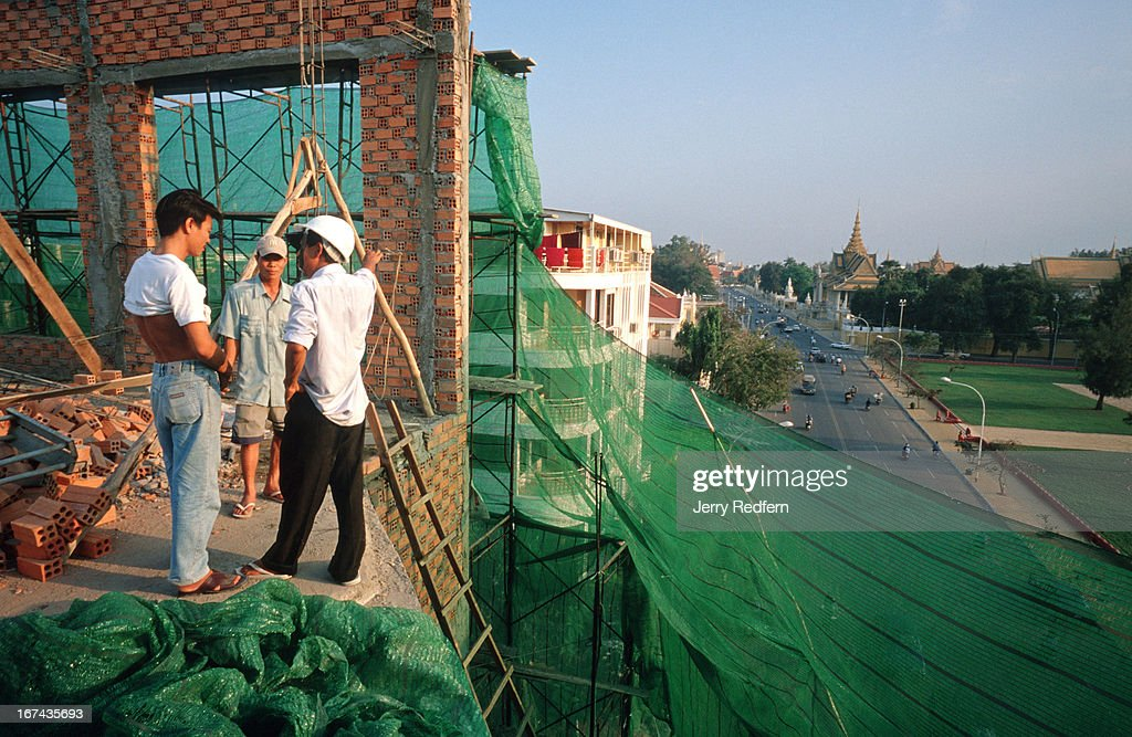A foreman and day laborers talk about work at the end of the day on the work site of a re-furbished guesthouse in Phnom Penh. The men on the construction site make on average the equivalent of $1 USD a day. The Cambodian Royal Palace is visible in the background..