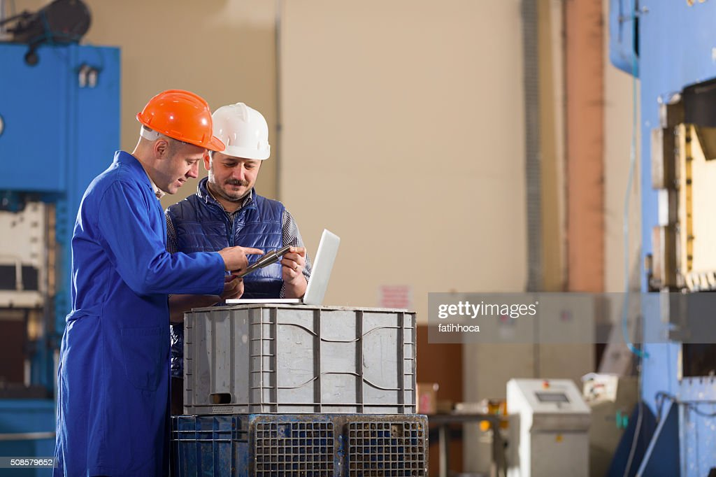 Foreman and engineer working in factory. : Stock Photo