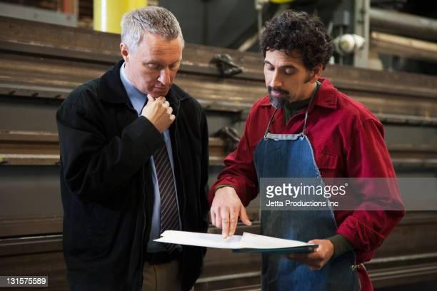 Foreman und Arbeiter Blick auf Papierkram in Fabrik