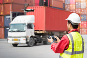Foreman control drone to fly to survey the area worth in container yard