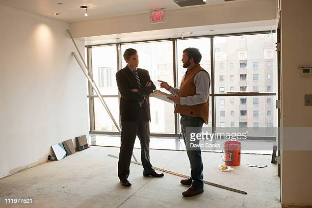 Foreman talks to architect in empty room