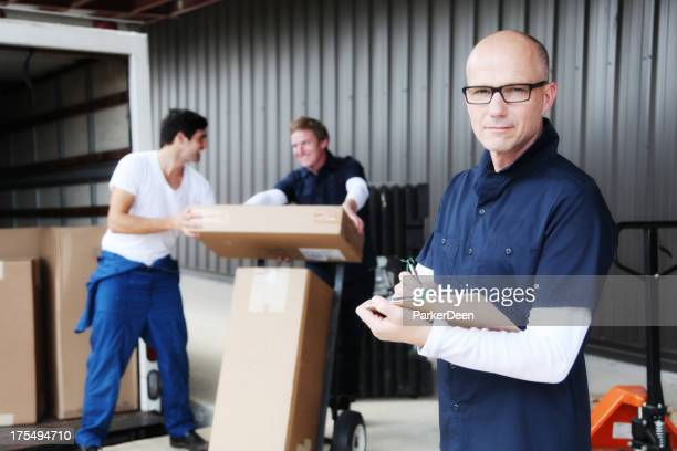 Contremaître avec le presse-papiers et travailleurs de chargement camion en mouvement