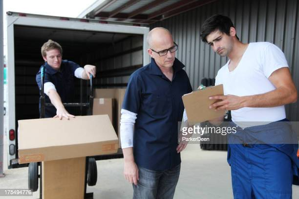 Foreman with Clipboard, and Workers Loading Moving Truck