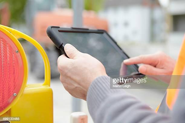 Foremans hands using digital tablet on road construction site