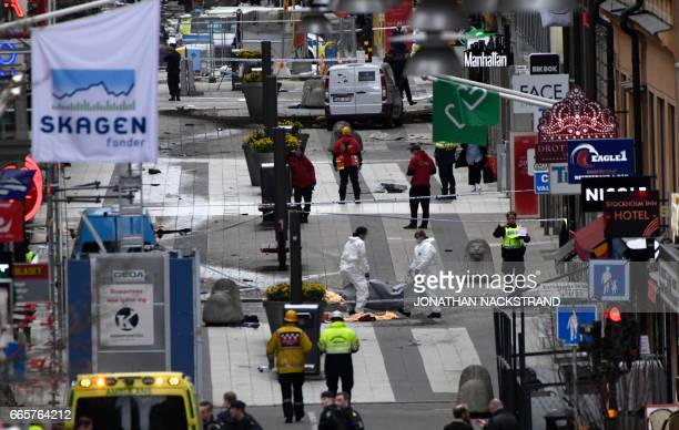Forensic agents move one of the bodies at the scene where a truck crashed into the Ahlens department store at Drottninggatan in central Stockholm...