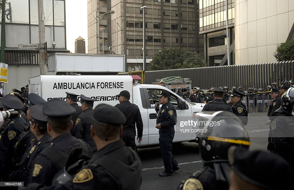 A forensic ambulance arrives on the premises of the skyscraper that houses the headquarters of state-owned Mexican oil giant Pemex in Mexico City on January 31, 2013, following a blast inside the building. An explosion rocked the skyscraper, leaving up to now 14 dead and 40 injured, as a plume of black smoke billowed from the 54-floor tower, according to official sources. AFP PHOTO/Yuri CORTEZ