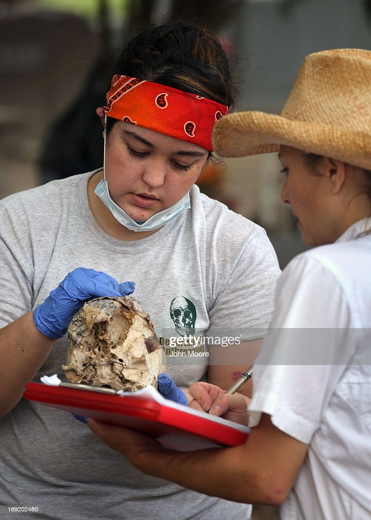 Forensic anthropology student Katherine Fernandez (L) from Baylor University helps to unearth the remains of unidentified immigrants from a cemetery on May 21, 2013 in Falfurrias, Texas. Teams from Baylor University and the University of Indianapolis are exhuming the bodies of more than 50 immigrants who died, mostly from heat exhaustion, while crossing illegally from Mexico into the United States. The bodies will be examined and cross checked with DNA sent from Mexico and Central American countries, with the goal of reuniting the remains with families. In Brooks County alone, at least 129 immigrants perished in 2012, the highest rate in the United States, according to forensic anthropologists.